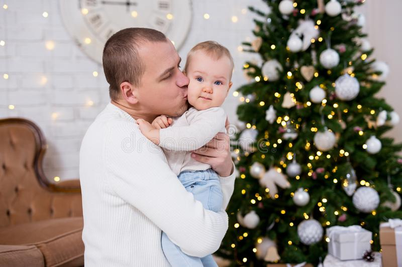 Christmas and family concept - portrait of happy father kissing his little girl near decorated christmas tree. Christmas and family concept - portrait of happy stock images