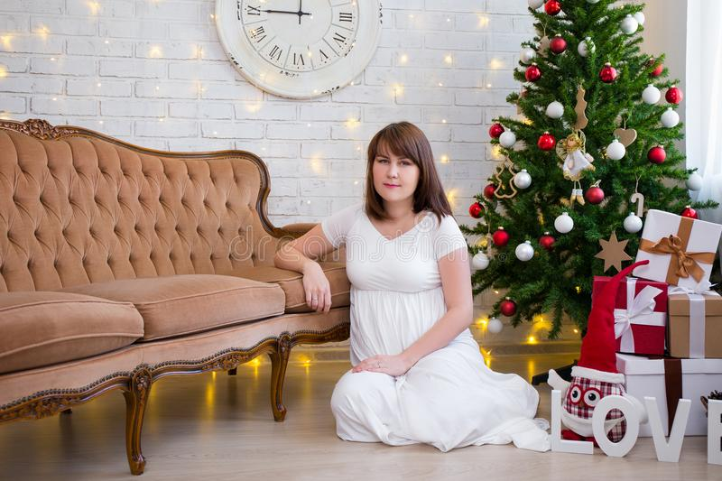 Christmas and family concept - pregnant woman at home with decor. Christmas and family concept - beautiful pregnant woman at home with decorated christmas tree stock image