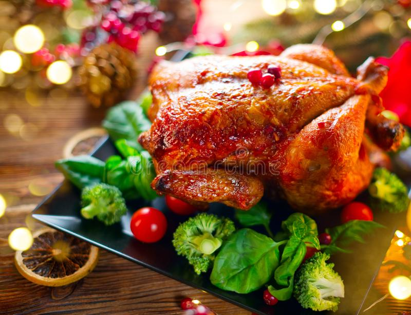 Christmas family dinner. Roasted chicken on holiday served table, decorated with gifts and burning candles. Roasted turkey stock image