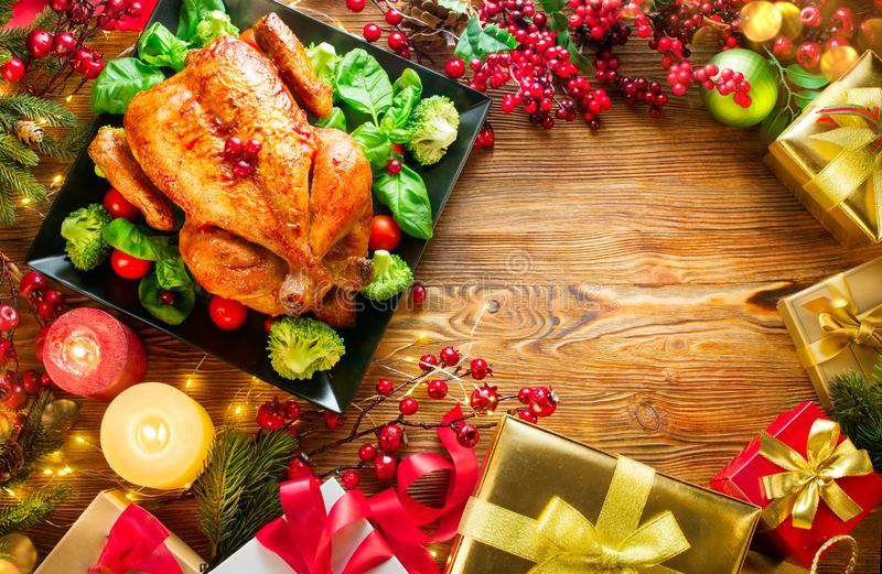Christmas family dinner. Roasted chicken on holiday table, decorated with gift boxes, burning candles and garlands royalty free stock image