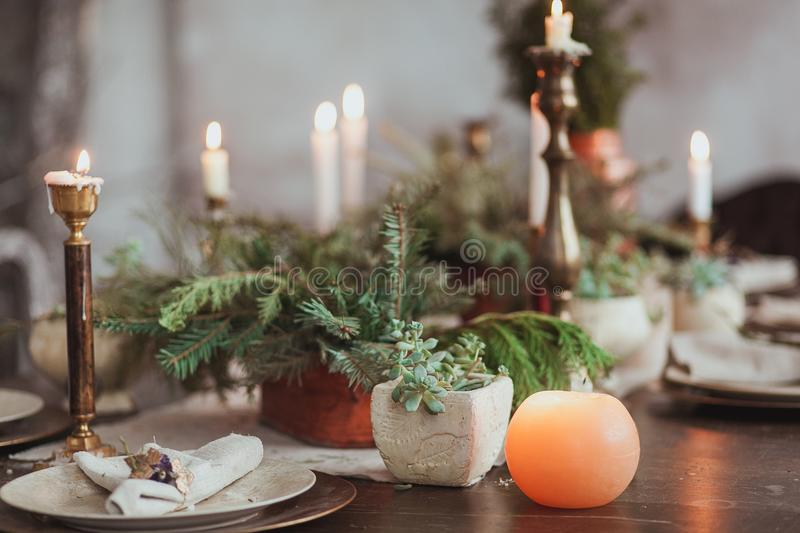 Christmas Family Dinner Table Concept. Candles, vintage dishes, fir branches with clear copy space on wall.  royalty free stock photo