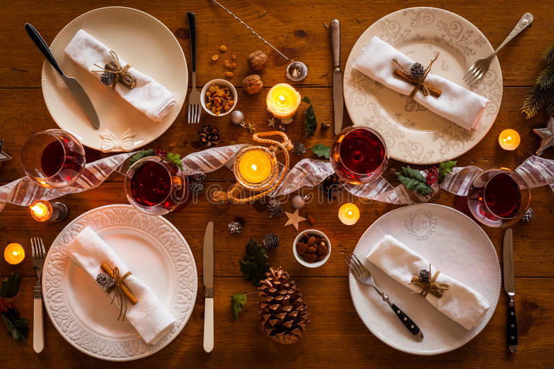 Christmas family dinner. Christmas table setting for family dinner at a cosy rustic table with candles and decorations. Top view stock photo