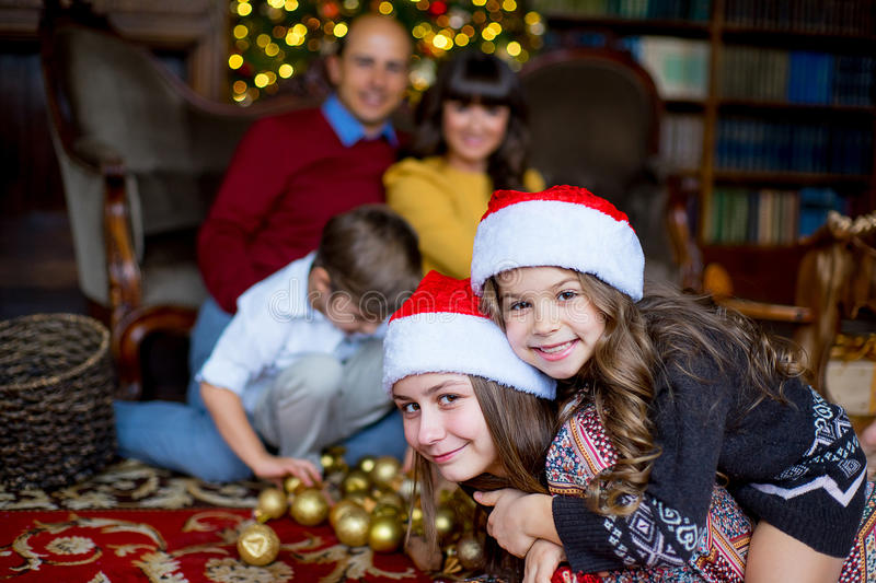 Christmas family of five people, happy parents and their kids. With gifts. First plan of two girls lying on the carpet. Christmas and New Year interior stock photos