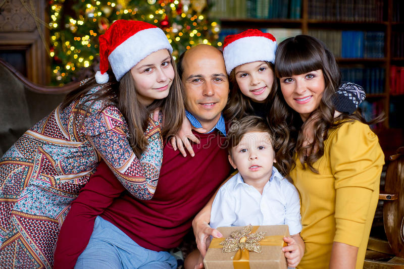 Christmas family of five people, happy parents and their kids. With gifts. Christmas and New Year interior stock image