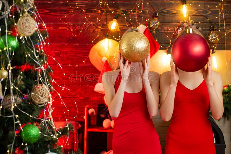 Christmas family fun. Christmas party. Women red dresses festive mood celebrate christmas hold big balls. Sisters having stock photo
