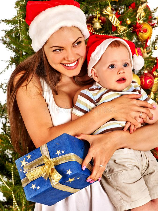 Christmas family with gift box under holiday tree. Mother and baby in Xmas hat on home party on isolated stock images