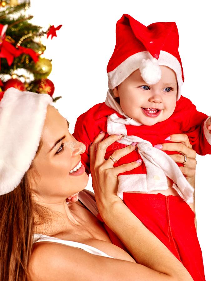 Christmas family with gift box under holiday tree. Christmas family under holiday tree. Mother and baby in Xmas hat on home party on isolated stock photo