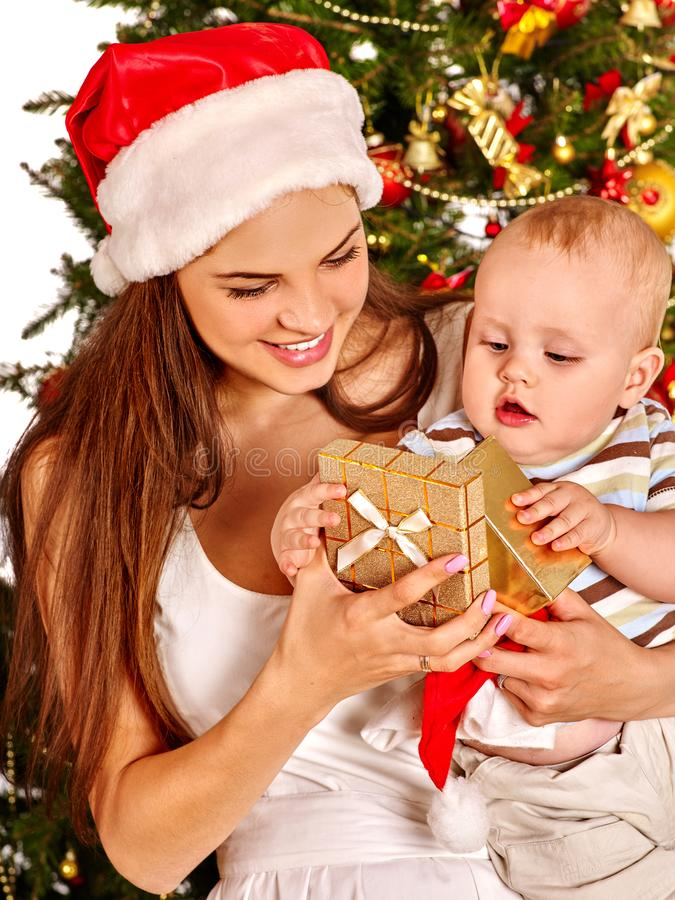 Christmas family with gift box under holiday tree. Mother and baby in Xmas hat on home party on isolated. New Year discounts for children`s products stock image