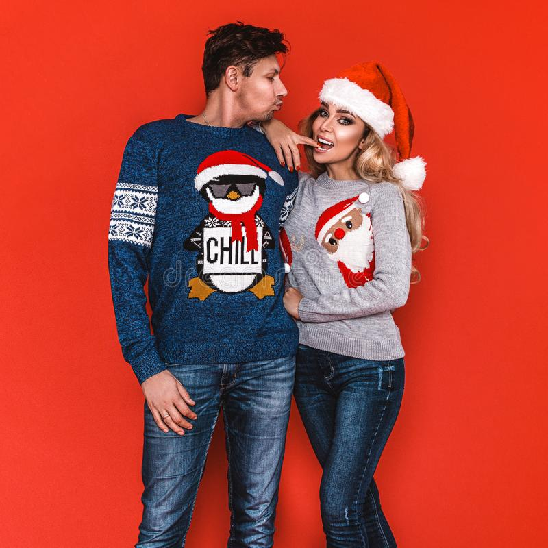Christmas family! Happy couple on Santa Claus hats on red background. Enjoyng love hugs, holidays people. Togetherness concept -. Image stock images