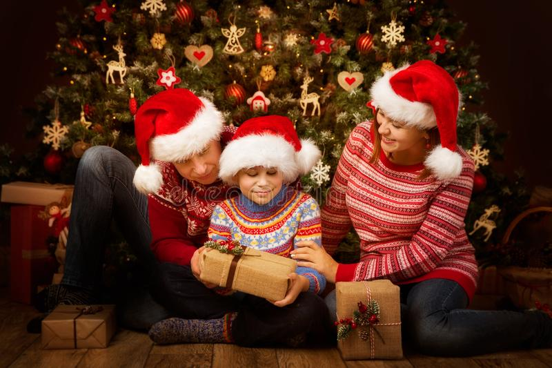Christmas Family Open Present Gift front of Xmas Tree, Happy Parents with Child in Santa Hats. Christmas Family Open Present Gift front of Xmas Tree, Happy royalty free stock images