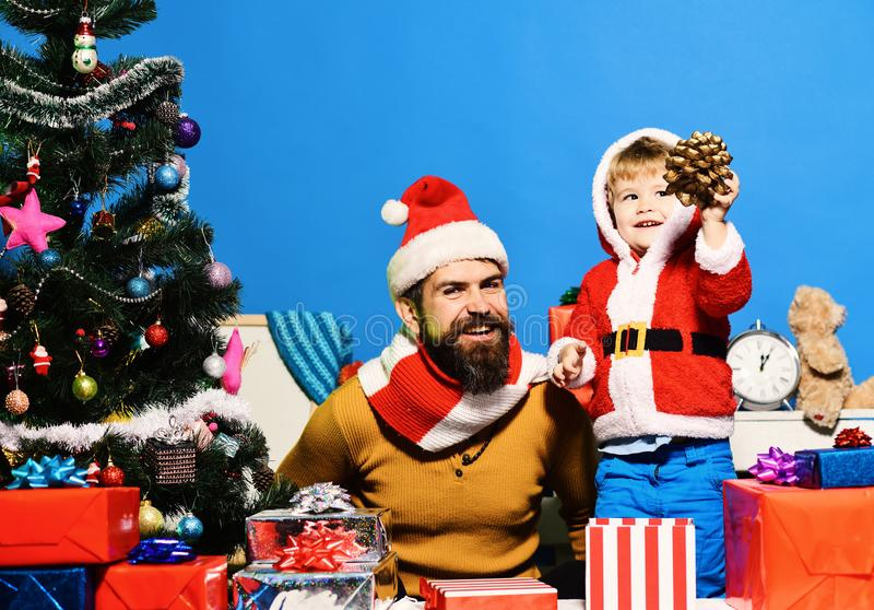 Christmas family opens presents on blue background. Boxing day and family concept. Boy holds fir tree cone playing with bearded father. Santa and little royalty free stock photos