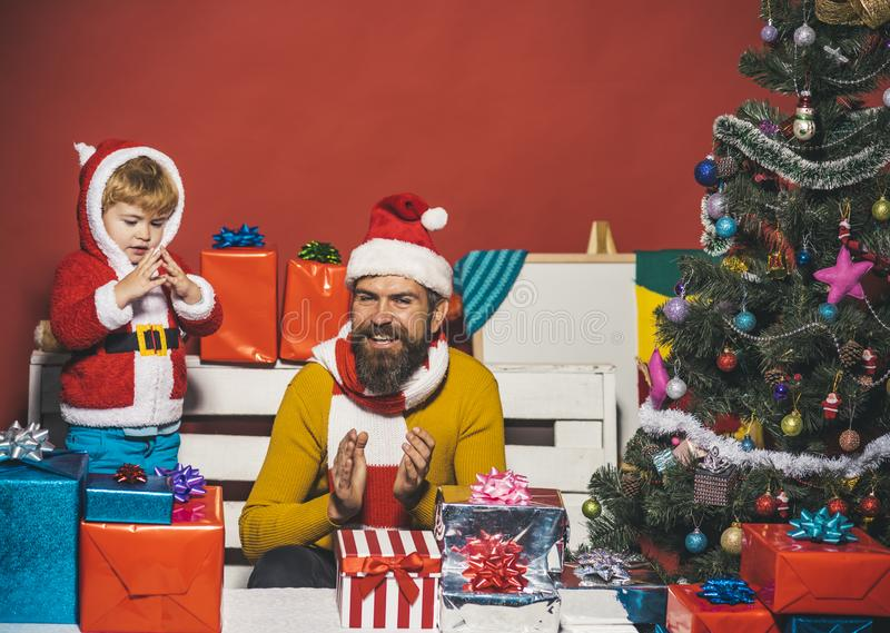 Christmas family opens presents on dark red background. Son and dad with beard and happy faces clap hands. Santa and little assistant among gift boxes near royalty free stock images