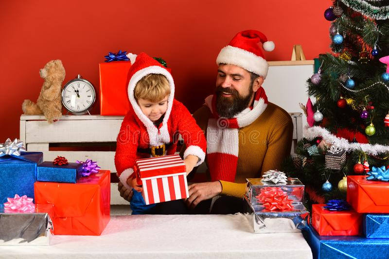 Christmas family opens presents on red background. Santa and little assistant among gift boxes near Christmas tree. Man with beard and happy face play with boy royalty free stock photography
