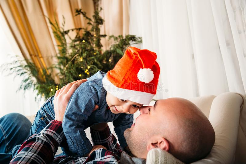 Christmas family portrait of happy smiling father playing with small kid in red santa hat. Winter holiday Xmas and New Year. Concept stock photography