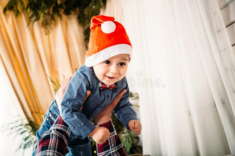 Christmas family portrait of happy smiling little boy in red santa hat in father`s hands. Winter holiday Xmas and New Year concept royalty free stock photo