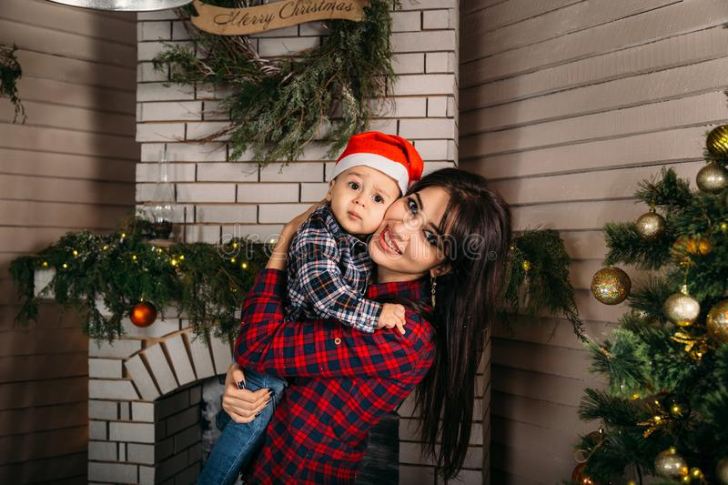 Christmas family portrait of happy smiling little boy in red santa hat in mother`s hands. Winter holiday Xmas and New Year concept.  stock photo