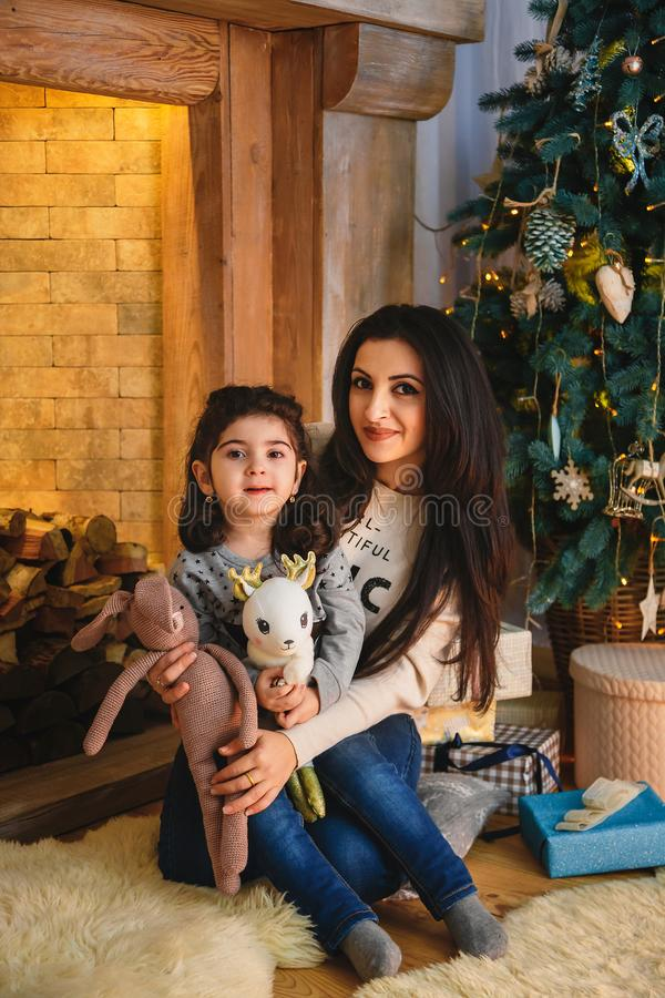 Christmas family portrait of happy smiling mother hugging small daughter near to christmas tree. Winter holiday Xmas and New Year royalty free stock images