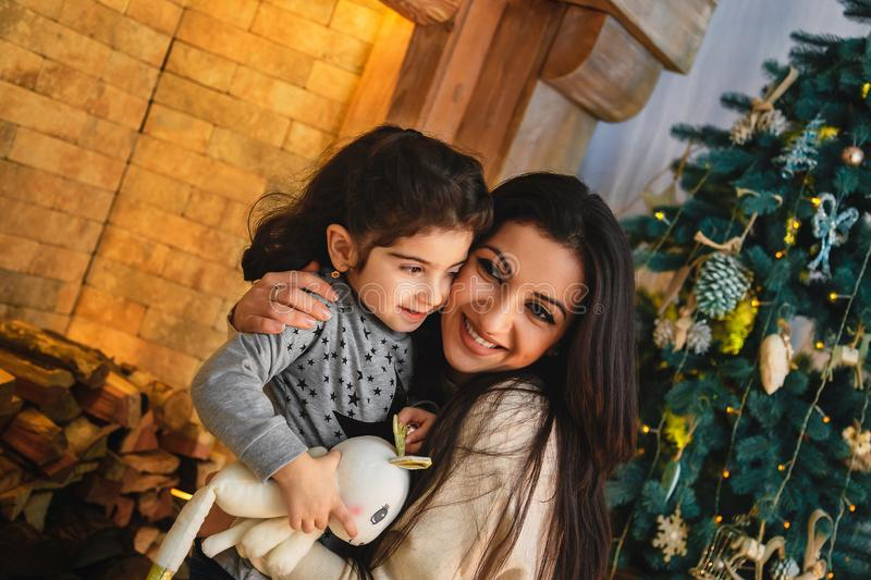 Christmas family portrait of happy smiling mother hugging small daughter near to christmas tree. Winter holiday Xmas and New Year stock photo