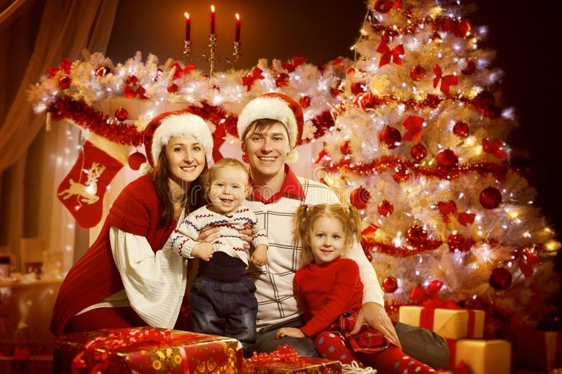 Christmas Family Portrait in Xmas Tree Interior Lights, New Year royalty free stock photography