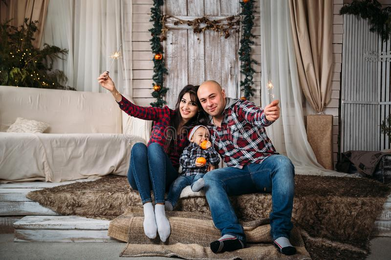 Christmas family portrait of young happy smiling parents with little kid in red santa hat holding sparklers. Winter holiday Xmas a royalty free stock photos
