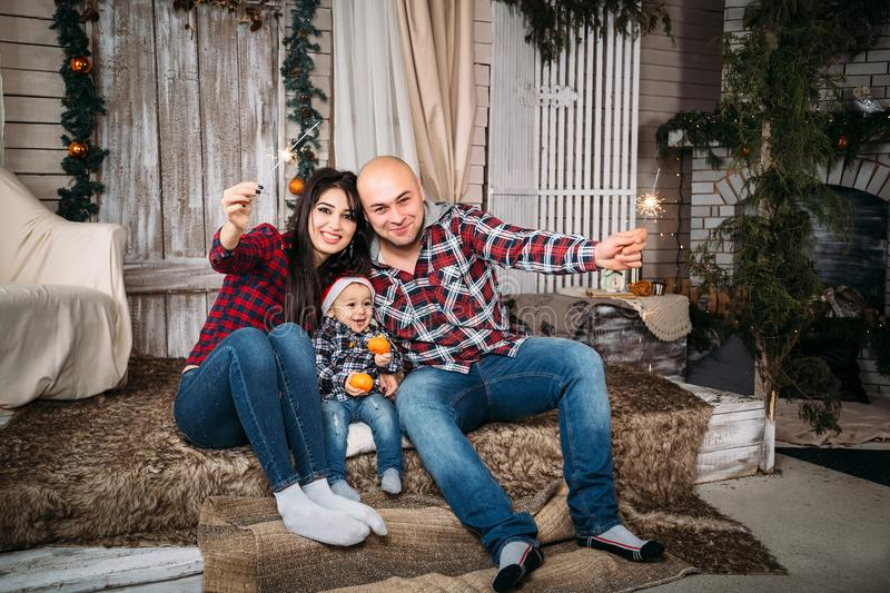 Christmas family portrait of young happy smiling parents with little kid in red santa hat holding sparklers. Winter holiday Xmas. And New Year concept stock image