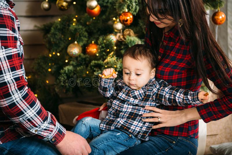 Christmas family portrait of young happy smiling parents playing with small child near the christmas tree. Winter holiday Xmas and stock photography