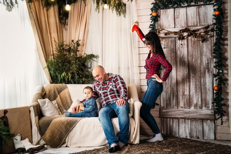 Christmas family portrait of young happy smiling parents playing with small kid. Winter holiday Xmas and New Year concept stock photos