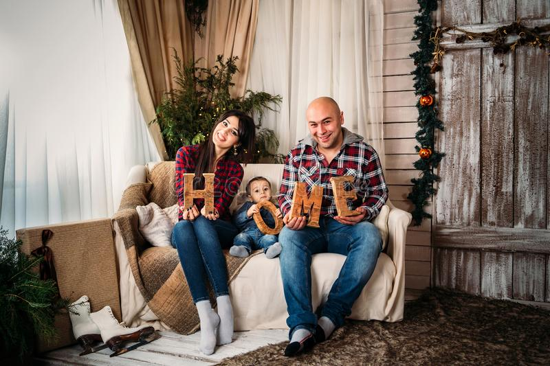 Christmas family portrait of young happy smiling parents and small kid sitting and holding wooden HOME decoration letters stock photos
