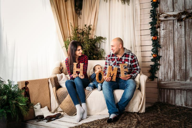 Christmas family portrait of young happy smiling parents and small son at home holiday living room stock photos