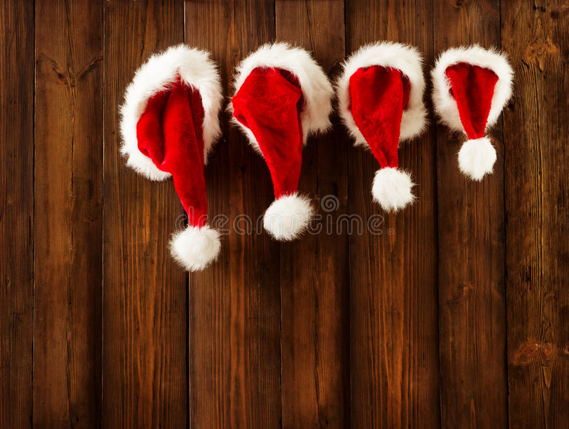 Christmas Family Santa Claus Hats Hanging on Wood Wall, Xmas Hat. Christmas Family Santa Claus Hats Hanging on Wood Wall, Xmas Kid Hat Hang on Decorated royalty free stock image