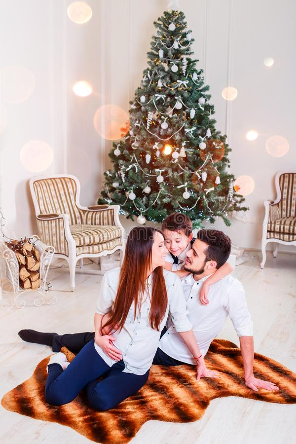 Christmas family smiling and kissing near the Xmas tree. Living room decorated by Christmas tree and present gift box. The light give cozy atmosphere. New Year stock photos