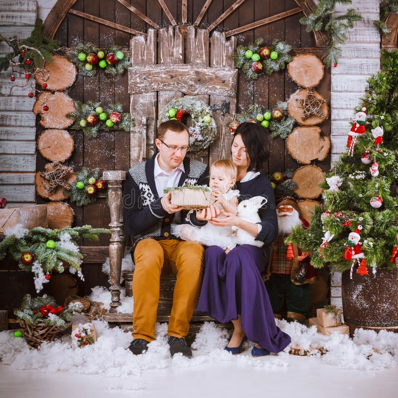 Christmas happy family of three persons and fir tree with gift boxes new year winter decorated background. Christmas family of three persons mother father and stock image