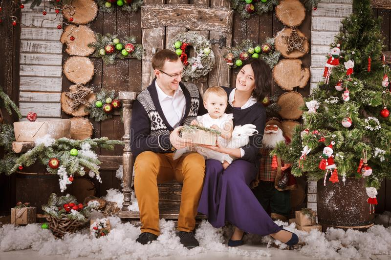 Christmas happy family of three persons and fir tree with gift boxes new year winter decorated background. Christmas family of three persons mother father and stock photo