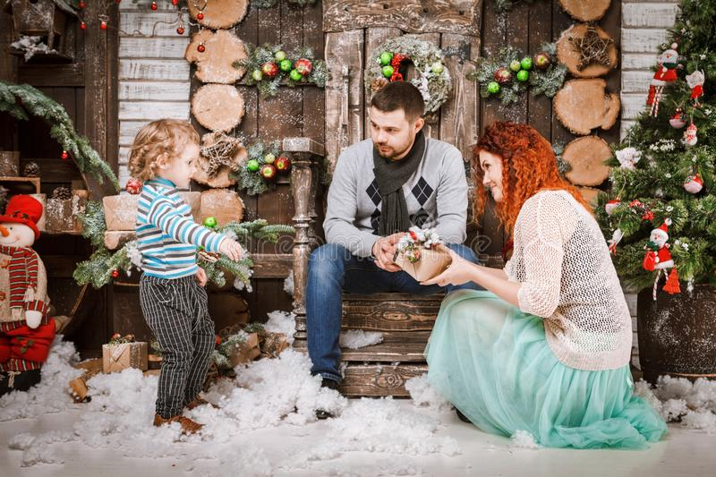 Christmas happy family of three persons and fir tree with gift boxes new year winter decorated background. Christmas family of three persons mother father and royalty free stock photo