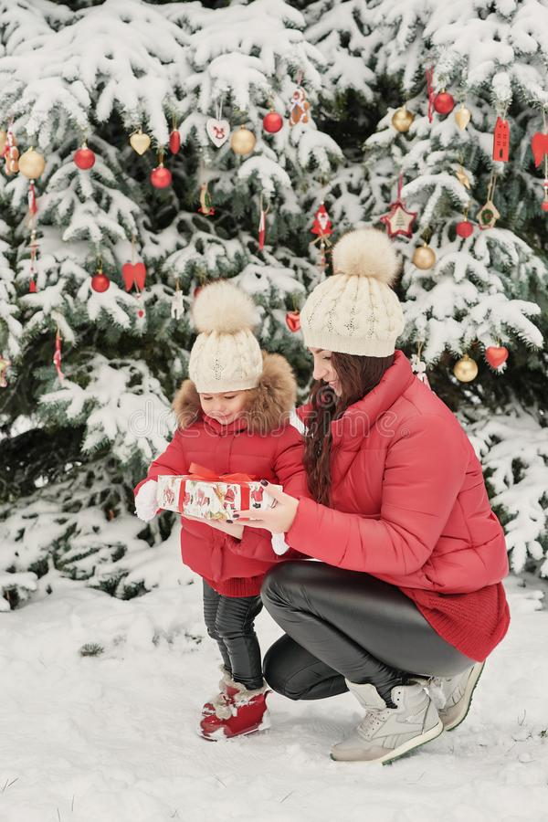 Christmas family in winter park. Happy family mother and child daughter having fun, playing at winter walk outdoors. Outdoor royalty free stock photography