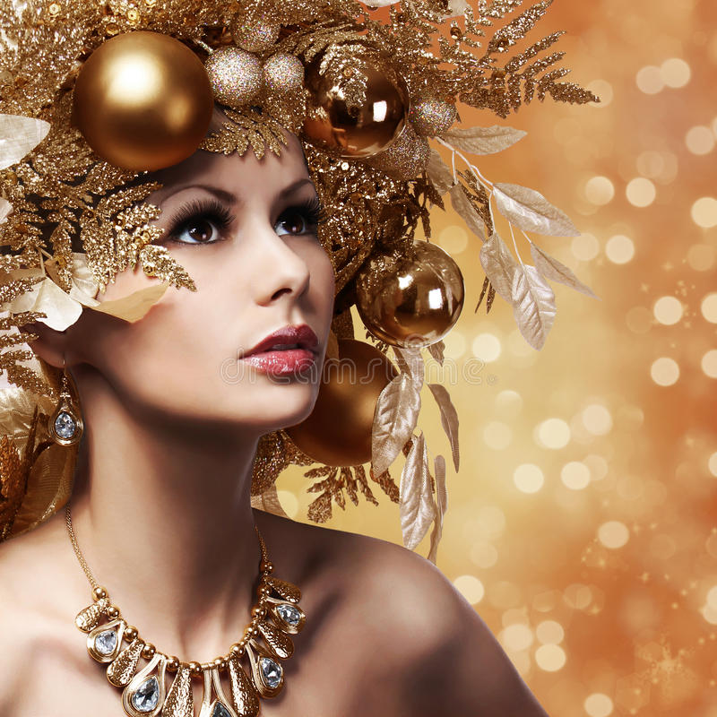 Christmas Fashion Girl with Decorated Hairstyle. Portrait. Of Beautiful Young Woman with Gold Christmas Balls. New Year royalty free stock photography