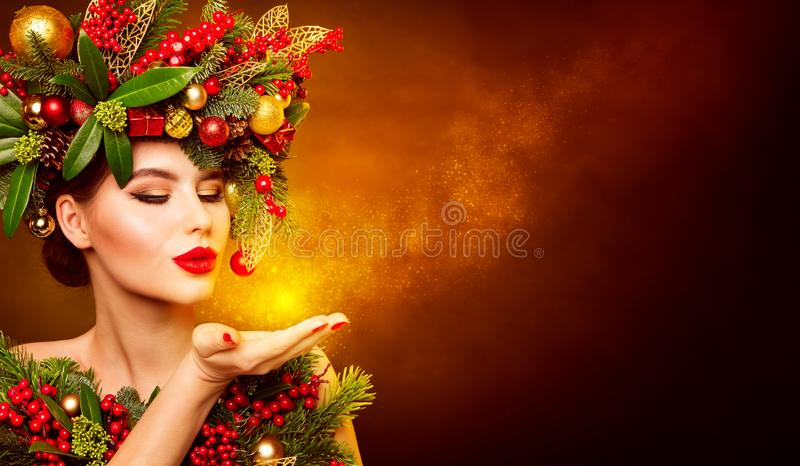 Christmas Fashion Model Beauty Makeup, Wreath Hairstyle. Xmas Woman Blowing to Hand, Beautiful Artistic Portrait stock images