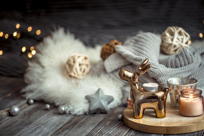 Christmas festive background with toy deer, blurred background with golden lights and candles, festive background on wooden deck. Christmas festive background royalty free stock photos