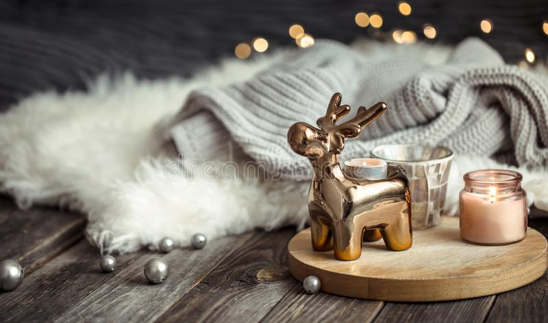 Christmas festive background with toy deer, blurred background with golden lights and candles, festive background on wooden deck. Christmas festive background stock photography