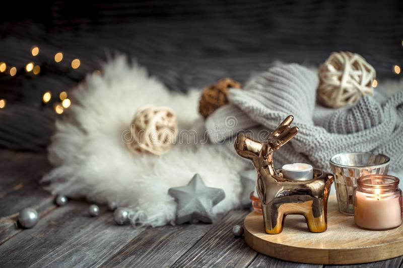 Christmas festive background with toy deer, blurred background with golden lights and candles, festive background on wooden deck. Christmas festive background stock image