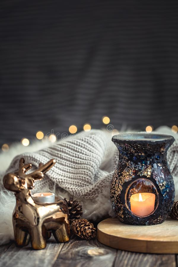 Christmas festive background with toy deer, blurred background with golden lights and candles, festive background on wooden deck. Christmas festive background stock photo