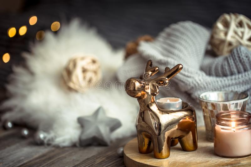 Christmas festive background with toy deer, blurred background with golden lights and candles, festive background on wooden deck. Table and winter sweater on royalty free stock photos