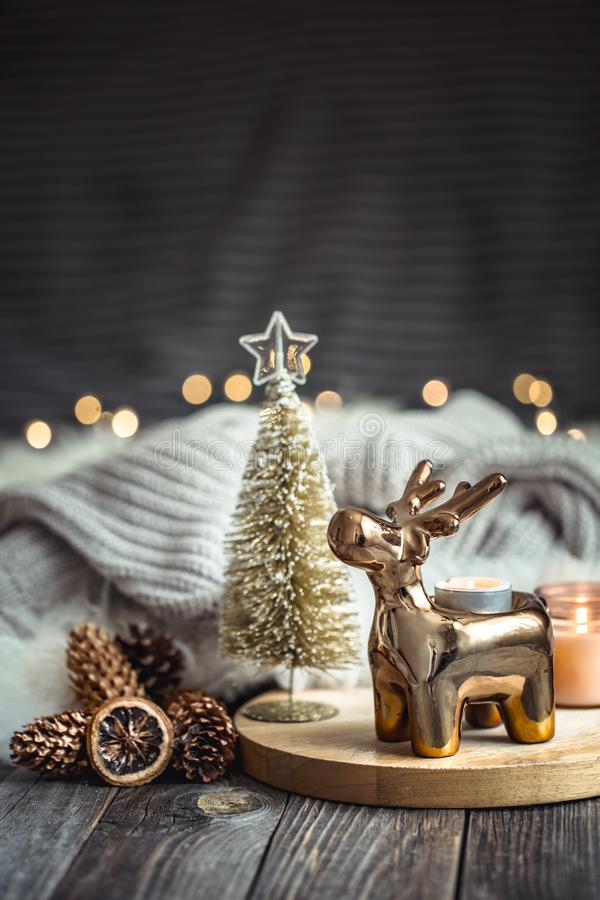Christmas festive background with toy deer, blurred background with golden lights and candles, festive background on wooden deck. Table and winter sweater on stock photo