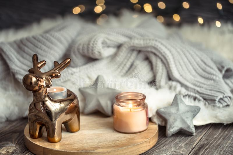 Christmas festive background with toy deer, blurred background with golden lights and candles, festive background on wooden deck. Table and winter sweater on stock photos