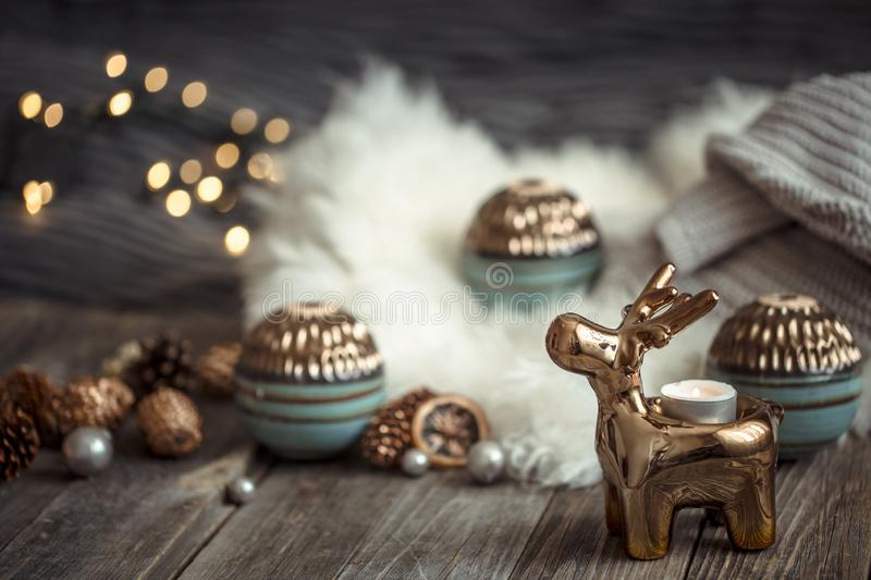 Christmas festive background with toy deer, blurred background with golden lights, festive background on wooden deck table. Christmas festive background with toy stock photography