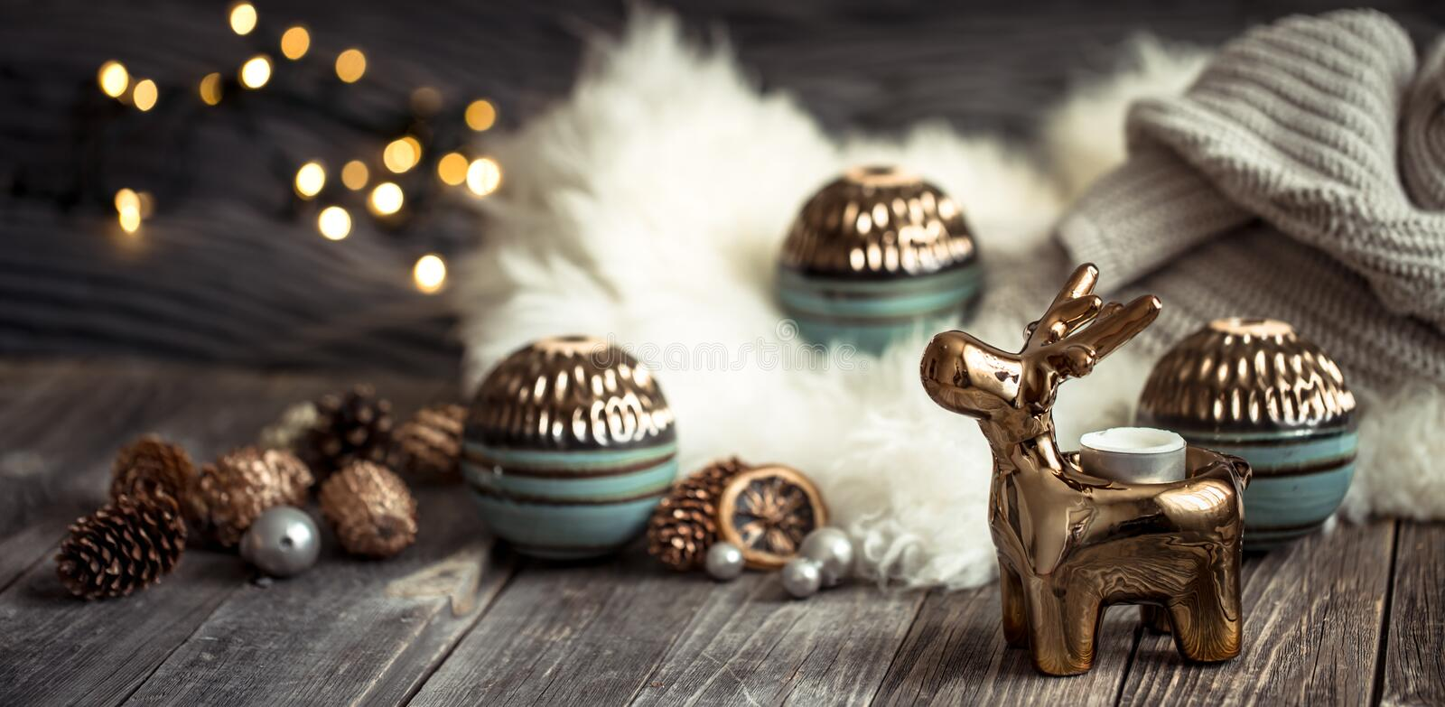 Christmas festive background with toy deer, blurred background with golden lights, festive background on wooden deck table. Christmas festive background with toy stock image