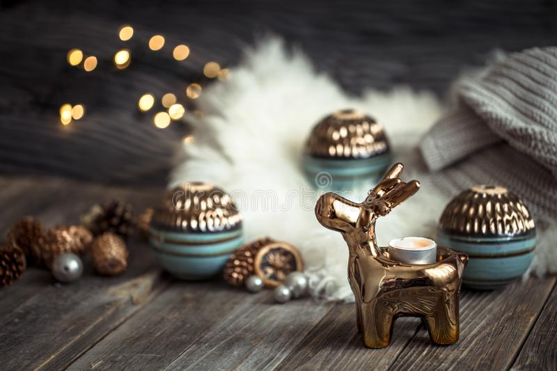 Christmas festive background with toy deer, blurred background with golden lights, festive background on wooden deck table. Christmas festive background with toy royalty free stock photography