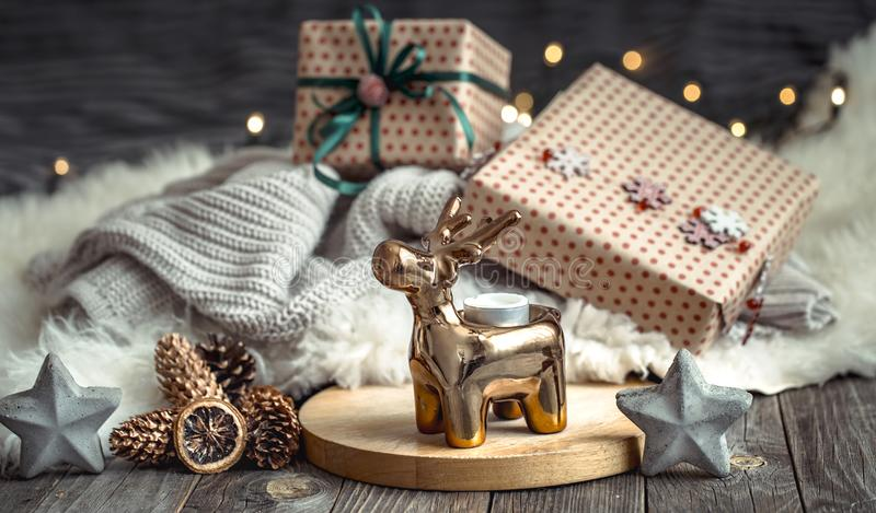Christmas festive background with toy deer with a gift box and Christmas tree, blurred background with golden lights on wooden. Christmas festive background with stock photography