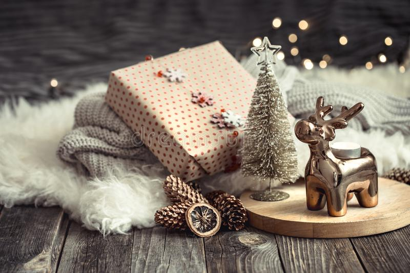 Christmas festive background with toy deer with a gift box and Christmas tree, blurred background with golden lights on wooden. Christmas festive background with stock image