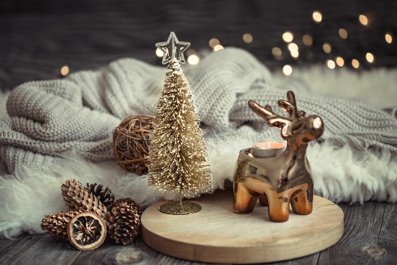 Christmas festive background with toy deer with a gift box and Christmas tree, blurred background with golden lights on wooden. Christmas festive background with stock photos